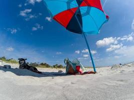 färgrikt paraply på solig dag på stranden foto