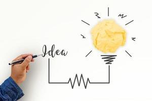 kreativitetsinspiration, idéer och innovationskoncept med glödlampa och pappers skrynklig boll. hand av affärsman som skriver textidé med pennan. foto