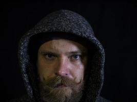 porträtt av en man med skägg och mustasch i huven med ett seriöst ansikte på en svart bakgrund foto