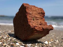 röd tegel på stranden mot bakgrund av havet och blå himmel foto