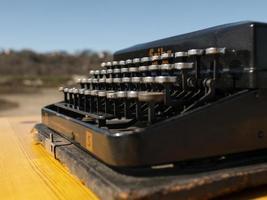 vintage skrivmaskin på ett träbord, handgjord på en blå himmel bakgrund foto