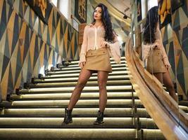 vacker modeflicka med långa ben som poserar på trappan inomhus foto