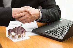 mäklare och kund handskakar över fastighetskontrakt foto