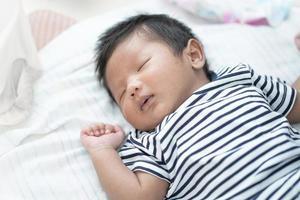 bedårande asiatisk sovande, liten spädbarn hälsosam sömn med varm ull vit filt hemma, baby vård koncept foto