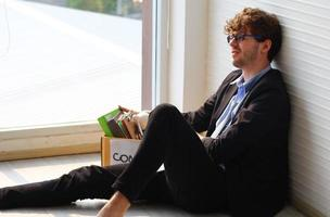 affärsman sparkad från jobbet, sittande, deprimerad och stressad från att få sparken. foto