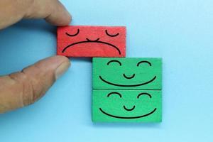 färgglada träklossar med känslomässigt ansikte. kundutvärdering och tillfredsställelse koncept. foto