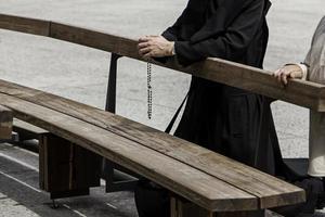 händerna på en präst med ett kors som ber foto