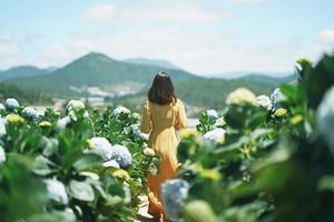 vacker asiatisk kvinna i gul klänning promenad i hortensia blommor trädgård foto