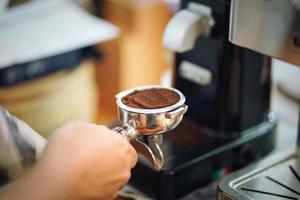 hand av barista håller portafilter fylld med malt kaffe som förbereder sig för att brygga med maskinen. selektivt fokus foto