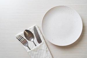 tom tallrik eller skål med kniv, gaffel och sked på träplattans bakgrund foto