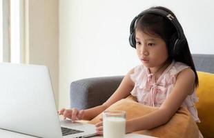 en ung asiatisk tjej som använder dator för att leran hemma som ett socialt distanseringsprotokoll under covid-19 eller coronaviruspandemi. hem skolgång koncept foto