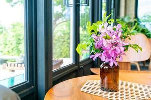 orkidéblommor i vasdekoration på bord i kaférestaurang foto