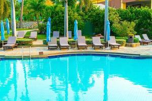 stolbassänger och paraplyer runt poolen med kokospalmer - helgdagar och semesterkoncept foto