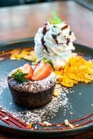 chokladkaka lava med jordgubbar och vaniljglass på svart tallrik foto