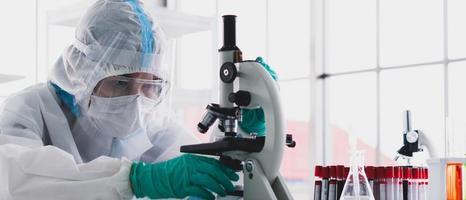 bannerbild av forskare i personlig skyddsutrustning eller person som forskar och experimenterar för att hitta läkemedel för att behandla covid-19 eller coronavirusinfektion i laboratoriet foto
