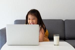 en ung asiatisk tjej som använder datorn för att lära sig hemma som ett socialt distanseringsprotokoll under covid-19 eller koronaviruspandemi. hemskolan koncept foto