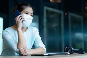 porträtt av ung asiatisk kvinna som bär ansiktsmask och hörlurar och använder datorn för att arbeta hemifrån under covid-19 eller coronavirusutbrott. social distansering och ny normal livsstilskoncept foto