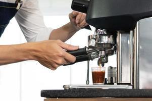 närbild bild av kaffebryggare som brygger expresso i en kopp i restaurangen. barista och kafé koncept foto