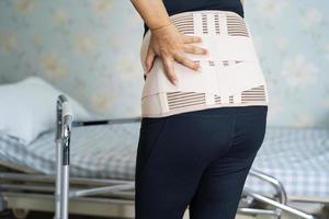 asiatisk dampatient som bär ryggvärkstödbälte för ortopedisk ländrygg med rullator. foto