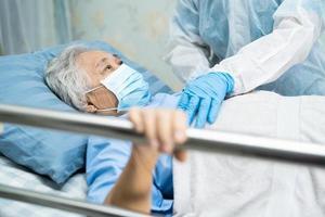 läkare som bär ppe-kostym för att kontrollera asiatisk senior eller äldre gammal damkvinnapatient som bär en ansiktsmask på sjukhus för att skydda infektion covid-19 coronavirus. foto