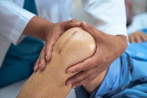 asiatisk senior eller äldre gammal damkvinnapatient visar hennes ärr kirurgisk total knäledsersättning sutur såroperation artroplastik på sängen i vårdavdelningen, hälsosamt starkt medicinskt koncept. foto