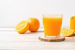 nytt apelsinjuiceglas på träbakgrund foto