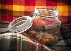 färgglada sockrade fruktgodisar i en glasburk foto