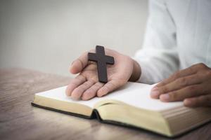 kvinna med kors i händer ber för välsignelse från gud på morgonen, andlighet och religion foto