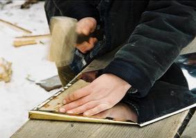 bilden visar en man med en hammare som slår den gula metallen foto