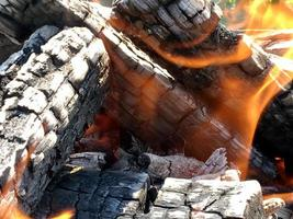 vacker röd flamma från träskiva, mörkgrå svarta kol inuti metallpanna foto