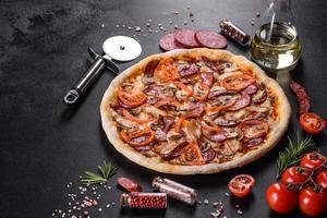 färsk läcker pizza gjord i en härdugn med korv, peppar och tomater foto