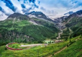 rött tåg bernina express till passagen i bergen. foto