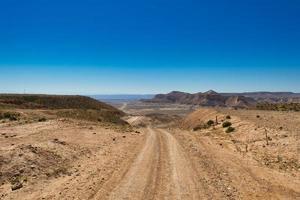grusväg in i öknen i israel foto