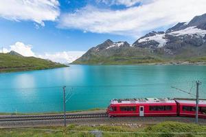 rött tåg i de höga bergen i de schweiziska alperna passerar nära en sjö foto