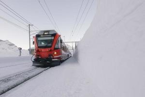 grisons röda tåg mitt i mycket snö foto
