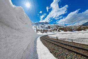snövägg för passage av den rhaetiska järnvägen på de schweiziska alperna foto