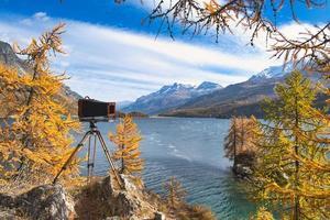 antik platta kamera på trä stativ under ett landskap foto