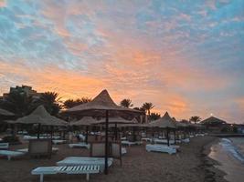 solstolar och halmparaplyer och vacker solnedgång på stranden i Hurghada, Egypten foto