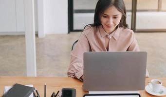 ung kvinna som sitter vid skrivbordet med bärbara datorn foto