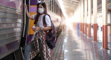 glad kvinnlig turist på järnvägsstationen foto