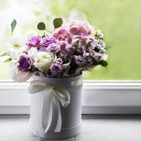 vackra blommor i en vit rund låda foto