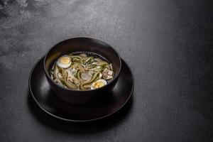 färsk läcker varm soppa med nudlar och vaktelägg i en svart tallrik foto