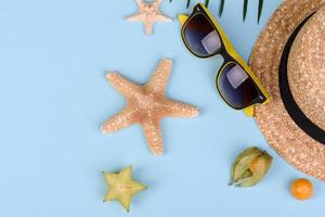 fruktkarambol, strandtillbehör och bladverk av en tropisk växt på färgat papper foto