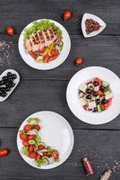 tre färska läckra sallader med kyckling, tomat, gurka, lök och gröna med olivolja foto