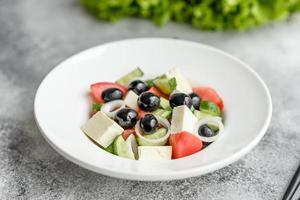 färsk läcker grekisk sallad med tomat, gurka, lök och oliver med olivolja foto
