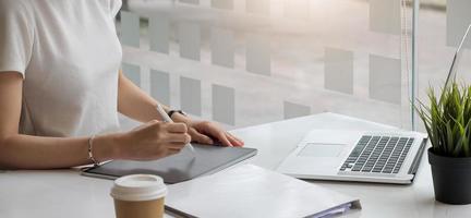 närbild av affärskvinna som arbetar på tabletten på kontoret foto