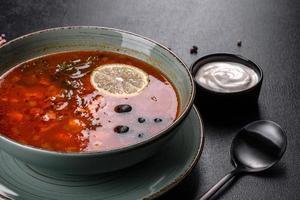läcker färsk varm soppa med tomat och kött i en keramisk tallrik. kål soppa foto