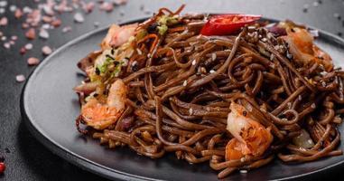 läcker färsk pasta med tomater, räkor och kryddor foto
