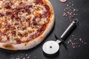 färsk läcker italiensk pizza med fyra typer av kött på en mörk betongbakgrund foto