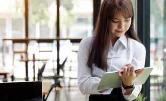 kvinna som använder en tablett på kontoret foto